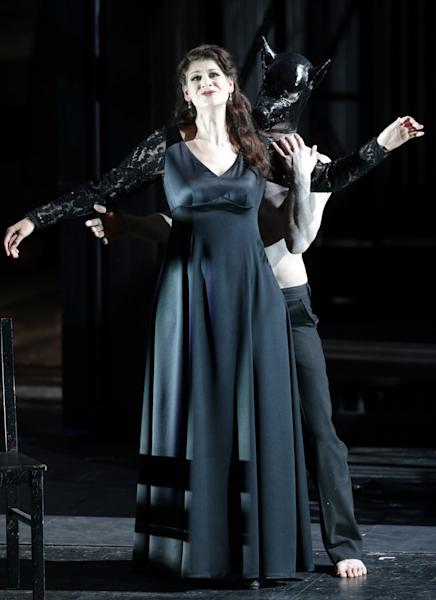 """In this picture taken Friday, June 21, 2013, Anja Harteros in the role of Leonora sings during a dress rehearsal for the opera """"Il Trovatore"""" by Giuseppe Verdi in the Bavarian State Opera House in Munich, southern Germany. This wild new production by Olivier Py opened the company's annual Munich Opera Festival. It's a non-stop barrage of nightmarish images mixing styles and periods that assault the audience at lightning speed on a multi-tiered revolving set. (AP Photo/Matthias Schrader)"""