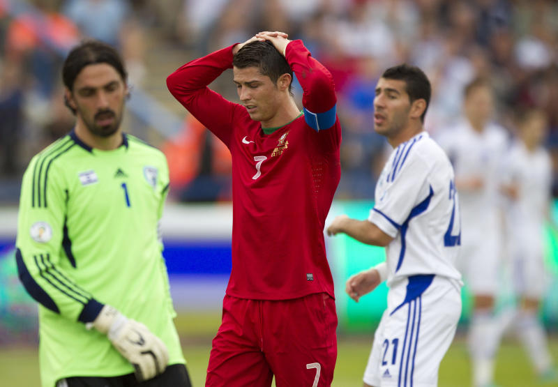 Portugal's Cristiano Ronaldo, center, holds his head as Israel's goalkeeper Dudu Aouate , left, and Israel's Eitan Tibi look on during 2014 World Cup group F qualifying soccer match in the Ramat Gan stadium near Tel Aviv, Israel, Friday, March 22, 2013. (AP Photo/Ariel Schalit)