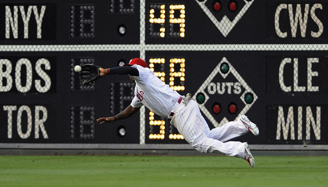 Philadelphia Phillies right fielder Marlon Byrd dives and catches a ball hit by San Francisco Giants' Hunter Pence during the first inning of a baseball game on Monday, July 21, 2014, in Philadelphia. (AP Photo/Michael Perez)