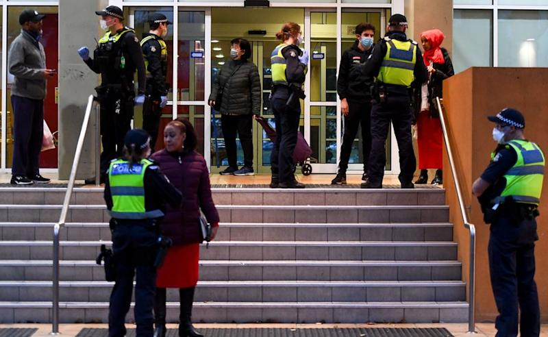 Police officers speaking to residents outside the entrance to one of the housing tower blocks