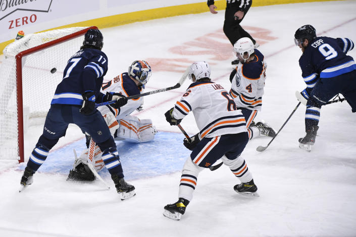 Winnipeg Jets' Andrew Copp (9) scores on Edmonton Oilers goaltender Mikko Koskinen (19) during the first period of an NHL hockey game Tuesday, Jan. 26, 2021, in Winnipeg, Manitoba. (Fred Greenslade/The Canadian Press via AP)