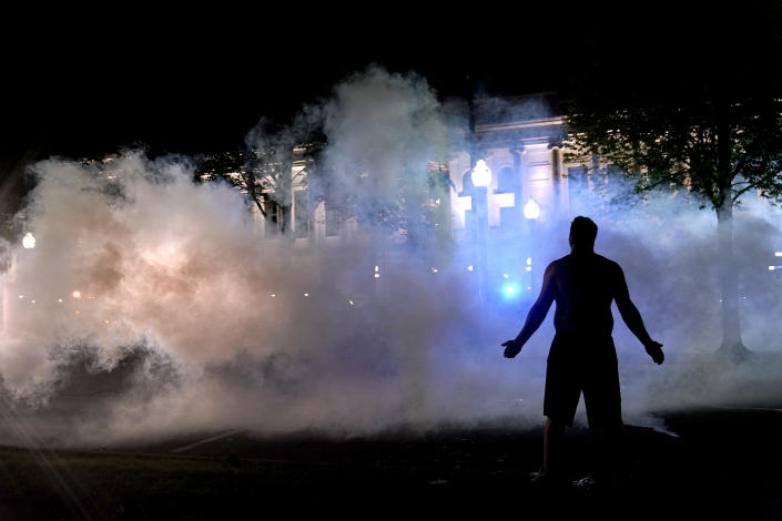 A protester attempts to continue standing through a cloud of tear gas fired by police outside the Kenosha County Courthouse, late Monday, Aug. 24, 2020, in Kenosha, Wis. Protesters converged on the county courthouse during a second night of clashes after the police shooting of Jacob Blake a day earlier turned Kenosha into the nation's latest flashpoint city in a summer of racial unrest. (AP Photo/David Goldman)