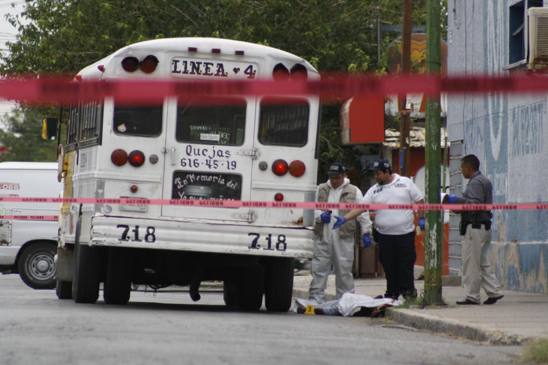"""In this Aug. 28, 2013 photo, forensic workers examine the scene where a bus driver was allegedly killed by a self-styled """"bus driver hunter,"""" in Ciudad Juarez, Mexico. Mexican prosecutors said Monday, Sept. 2, 2013, they are investigating claims that a woman who killed two bus drivers last week in this northern border city was seeking revenge for alleged sexual abuse of female passengers. (AP Photo/Raymundo Ruiz)"""