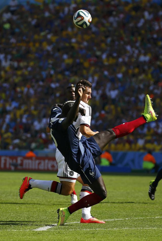 France's Mamadou Sakho (front) fights for the ball with Germany's Miroslav Klose during the 2014 World Cup quarter-finals soccer match at the Maracana stadium in Rio de Janeiro July 4, 2014. REUTERS/Pilar Olivares (BRAZIL - Tags: SOCCER SPORT WORLD CUP)