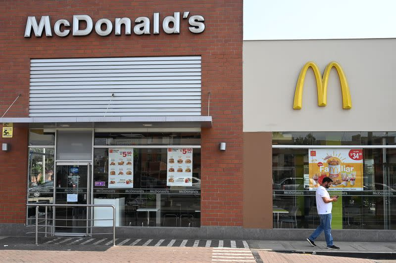 A person walks next to a closed McDonald's restaurant, one of all 29 locations that were closed following the deaths of two teenaged employees, in Lima