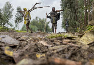 """Villagers carry wood on a path near the village of Chenna Teklehaymanot, in the Amhara region of northern Ethiopia Thursday, Sept. 9, 2021. At the scene of one of the deadliest battles of Ethiopia's 10-month Tigray conflict, witness accounts reflected the blurring line between combatant and civilian after the federal government urged all capable citizens to stop Tigray forces """"once and for all."""" (AP Photo)"""
