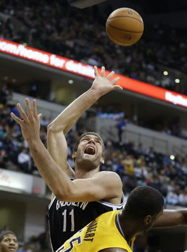 Brooklyn Nets center Brook Lopez, top, is fouled by Indiana Pacers center Roy Hibbert while shooting in the first half of an NBA basketball game in Indianapolis, Friday, April 12, 2013. (AP Photo/Michael Conroy)