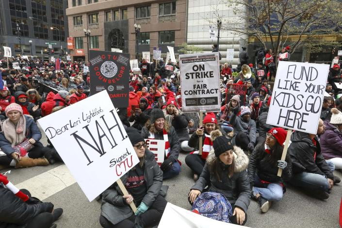 Striking Chicago teachers sit on La Salle Street outside City Hall on the fifth day of canceled classes Wednesday, Oct. 23, 2019, in Chicago. The protest was timed to coincide with Mayor Lori Lightfoot's first budget address. (AP Photo/Teresa Crawford)
