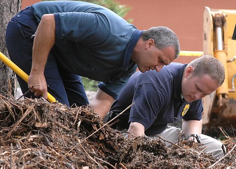 Doug Dupell, left, street maintenance supervisor for the City of Hickory and Hickory Police Investigator Rob Burwell sift through mulch at the home Zahra Baker for the second day in a row, Thursday, Oct. 28, 2010  in Hickory, N.C.. Law enforcement agencies are going through the residence and backyard for more evidence. (AP Photo/The Hickory Daily Record, Robert C. Reed)
