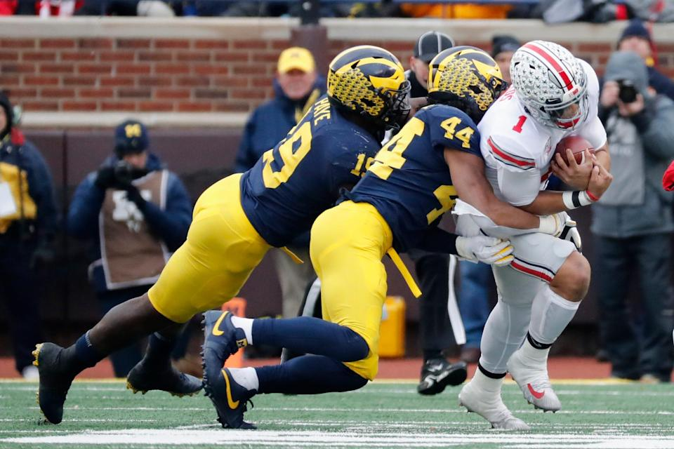 Ohio State quarterback Justin Fields is tackled by Michigan Wolverines linebacker Cameron McGrone (44) and defensive lineman Kwity Paye (19) in the first half at Michigan Stadium, Nov. 30, 2019 in Ann Arbor.