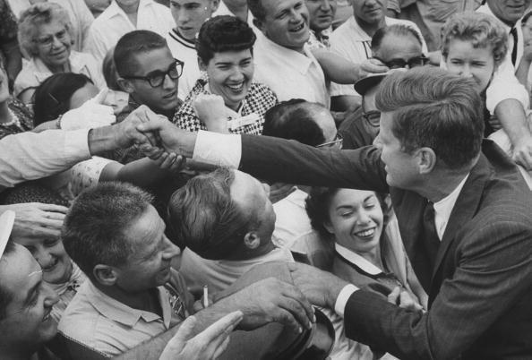 <p>Kennedy on the campaign trail, shaking as many hands as he can in a dense crowd.</p>