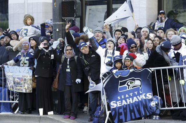 Seattle Seahawks fans cheer along the route of the Super Bowl champions parade on Wednesday, Feb. 5, 2014, in Seattle. The Seahawks beat the Denver Broncos 43-8 in NFL football's Super Bowl XLVIII on Sunday. (AP Photo/Ted S. Warren)