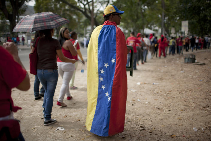 People queue outside the military academy to see the body of Venezuela's late President Hugo Chavez lying in state in Caracas, Venezuela, Sunday, March 10, 2013. Chavez died of cancer on March 5. He was 58. (AP Photo/Ariana Cubillos)