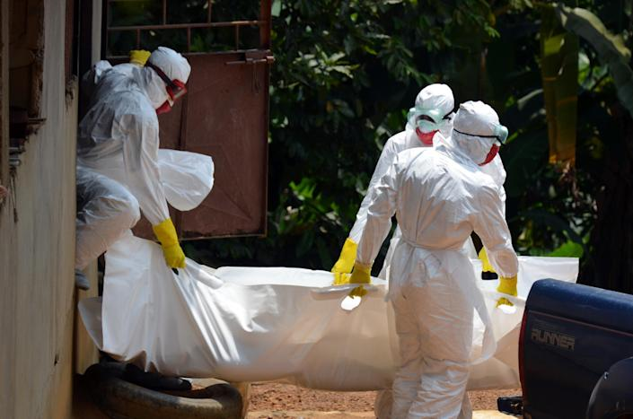 Liberian Red Cross health workers, wearing protective suits, carry the body of a 18-old-month baby, victim of the Ebola virus in a district of Monrovia on September 12, 2014 (AFP Photo/Zoom Dosso)