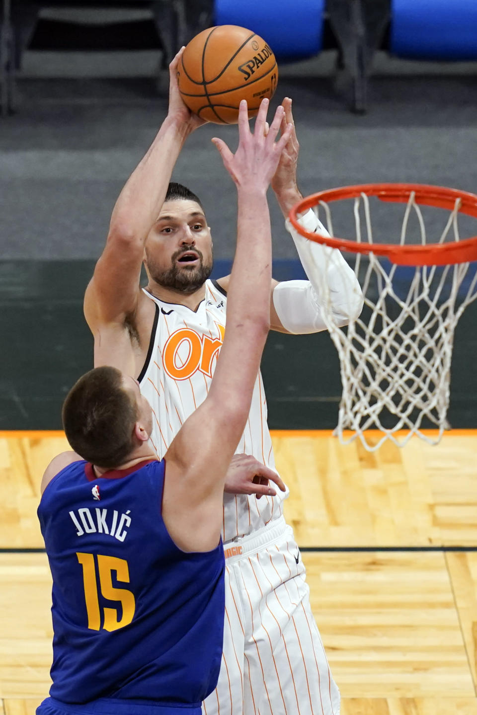 Orlando Magic center Nikola Vucevic, right, makes a shot over Denver Nuggets center Nikola Jokic (15) during the second half of an NBA basketball game, Tuesday, March 23, 2021, in Orlando, Fla. (AP Photo/John Raoux)