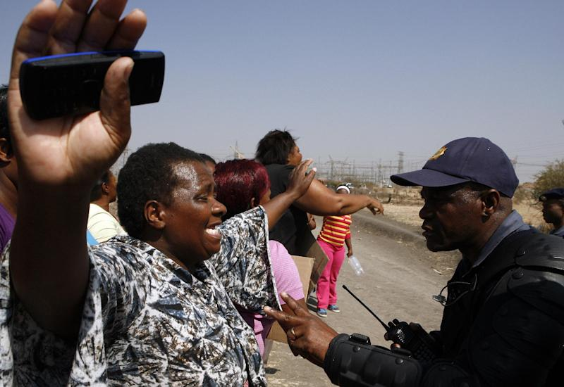 An unidentified woman protests against the police near a shooting scene at the Lonmin mine near Rustenburg, South Africa, Friday, Aug. 17, 2012. Police chief Mangwashi Victoria Phiyega says 34 miners died and another 78 were wounded when police opened fire on strikers in one of the worst police shootings in South Africa since apartheid. (AP Photo/Themba Hadebe)