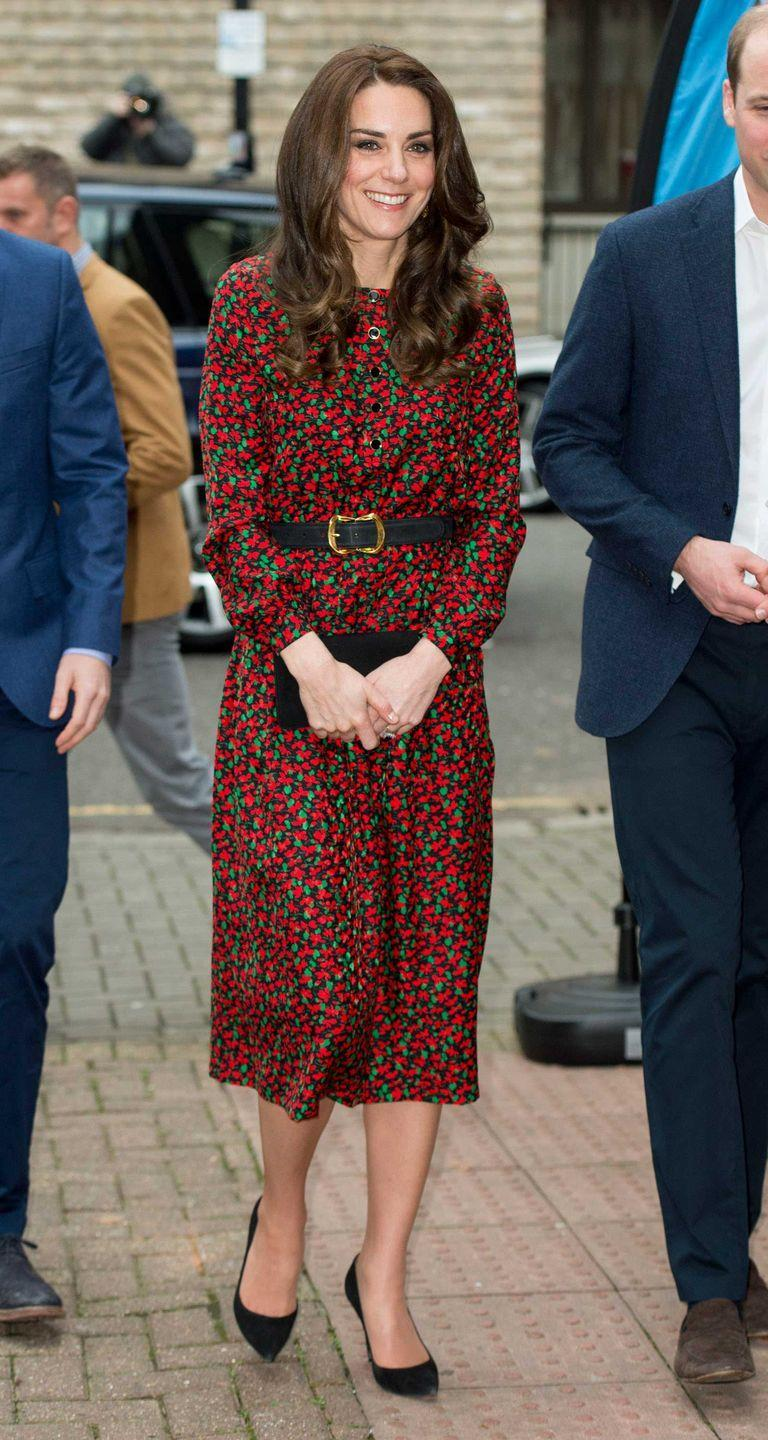 <p>Duchess Kate attends a Christmas party for volunteers at the Mix wearing a festive red-and-green printed Vanessa Seward dress with a simple black clutch and pumps. </p>