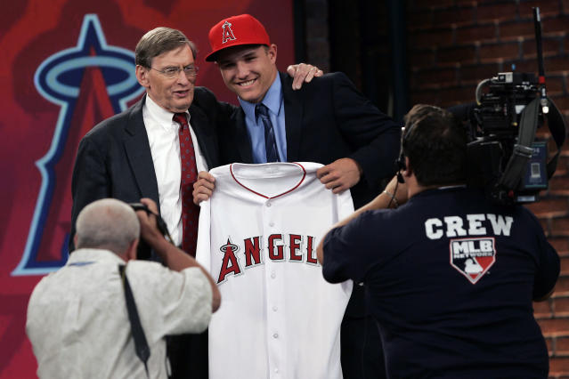 FILE - In this June 9, 2009, file photo, Baseball Commissioner Bud Selig poses with Mike Trout, an outfielder from New Jersey's Millville High School, who was picked 25th by the Los Angeles Angels in the baseball draft in Secaucus, N.J. Baseball's amateur draft this week will look much different because of the coronavirus pandemic, and more permanent changes could be coming soon. (AP Photo/Rich Schultz, File)