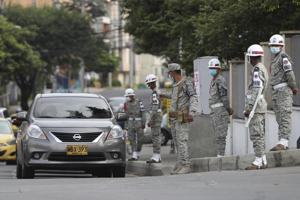 Soldiers stand guard outside the military hospital where Defense Minister Carlos Holmes Trujillo died from complications of COVID-19 in Bogota, Colombia, Tuesday, Jan. 26, 2021. President Ivan Duque said that Trujillo died early Tuesday. (AP Photo/Fernando Vergara)
