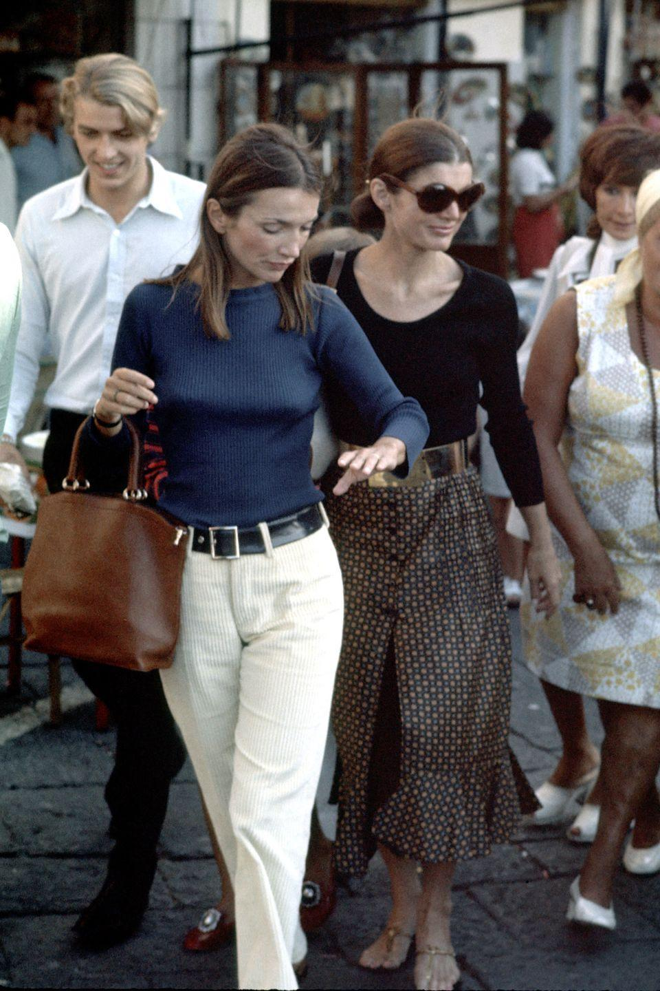 <p>These sisters have Italian vacation style on lock. Jackie wears a belted polka dot maxi skirt, while Lee goes for khaki trousers and a navy top in Capri.</p>