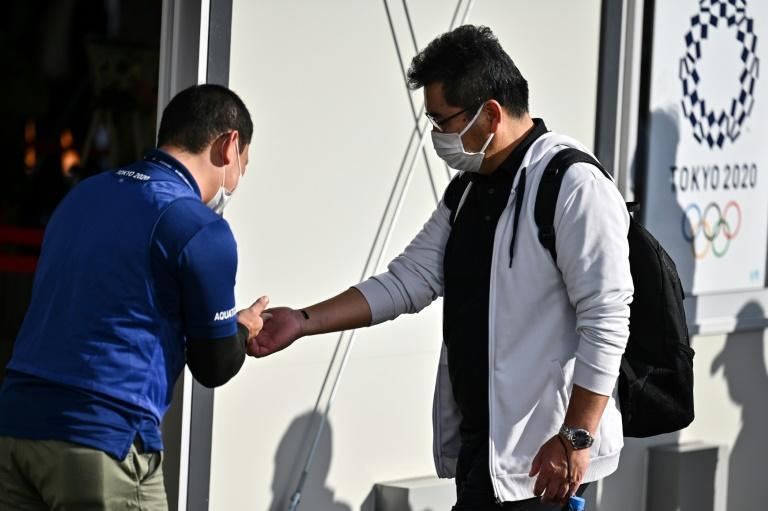 A volunteer checks the body temperature of a volunteer acting as a spectator during a test of potential spectator and games screening measures