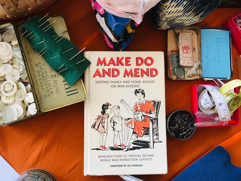 Sarah Klymkiw's fashion repair table, complete with needles, buttons, spare bits of fabric and a vintage guide to mending. The equivalent of a garbage truck full of textiles gets sent to a landfill or burned every second. (Tess Riley for HuffPost)