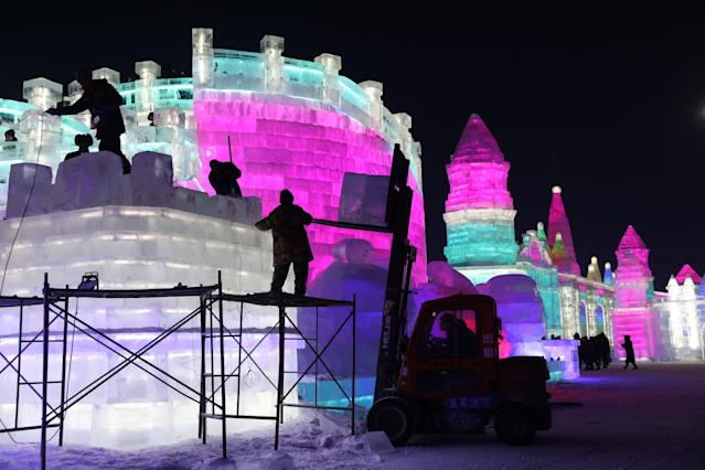 <p>Workers carve ice sculptures one day ahead of the opening of the 34th Harbin International Ice and Snow Festival in China's Heilongjiang province on Jan. 4. (Photo: Wu Hong/EPA-EFE/REX/Shutterstock) </p>
