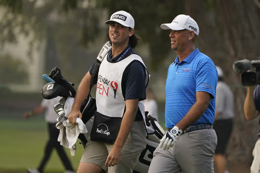 FILE - Stewart Cink, right, walks with his caddie and son, Reagan Cink, down the 18th fairway of the Silverado Resort North Course during the final round of the Safeway Open PGA golf tournament in Napa, Calif., in this Sunday, Sept. 13, 2020, file photo. Cink said having his son as a caddie will mean more practice rounds this year, and it's worth it to him. (AP Photo/Eric Risberg, File)