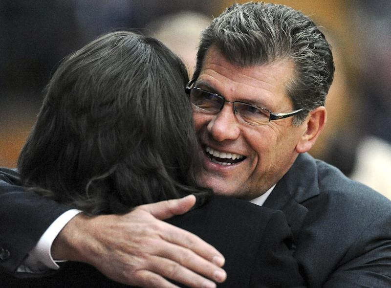 Connecticut head coach Geno Auriemma, right, hugs Hartford head coach Jennifer Rizzotti, left, before a NCAA women's college basketball game in West Hartford, Conn., Saturday, Dec. 22, 2012. Connecticut won 102-45. (AP Photo/Jessica Hill)
