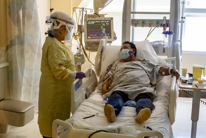 COLTON, CA - JULY 8, 2020: ICU nurse Lynda Tegan checks on COVID-19 patient Jose Mariscal, 66, who has been in the ICU for four days at Arrowhead Regional Medical Center on July 8, 2020 in Colton, California. This ICU has only 2 more beds available for Covid patients, but has the capacity to expand to more beds if needed.(Gina Ferazzi / Los Angeles Times)
