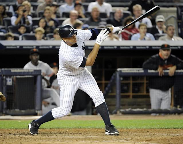 New York Yankees' Alex Rodriguez follows through on a grand slam during the seventh inning of an interleague baseball game against the San Francisco Giants, Friday, Sept. 20, 2013, at Yankee Stadium in New York. (AP Photo/Bill Kostroun)