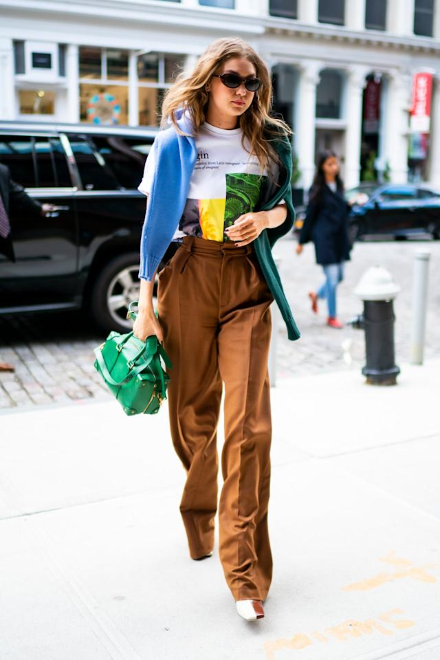 <p>Gigi styled her two-toned Isa boots with high-waisted trousers, a graphic tee, and a hoodie swung over her shoulders.</p>
