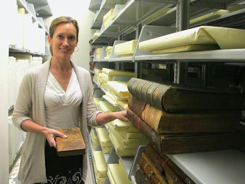 Archivist Trisha Kometer poses for a photo with a rare 1743 book in the vault at the Charleston Library Society in Charleston, S.C., on Monday, May 7, 2012. The volume, which was found in the vault of the Charleston Library Society, really belongs to the College of Charleston and will be turned over to officials from the college at a ceremony later this week. (AP Photo/Bruce Smith)