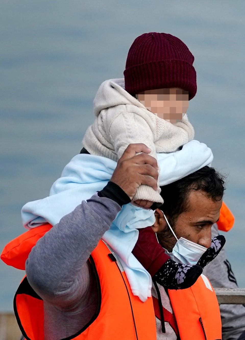 A man carrying a baby wrapped in blanket was among a group who were brought ashore in Kent on Friday (Gareth Fuller/PA) (PA Wire)