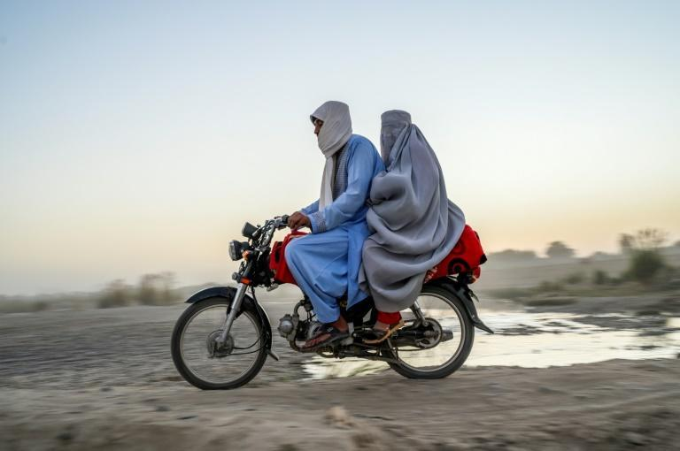 A woman wearing a burqa rides on the back of a mortorbike in Kandahar (AFP/Bulent KILIC)