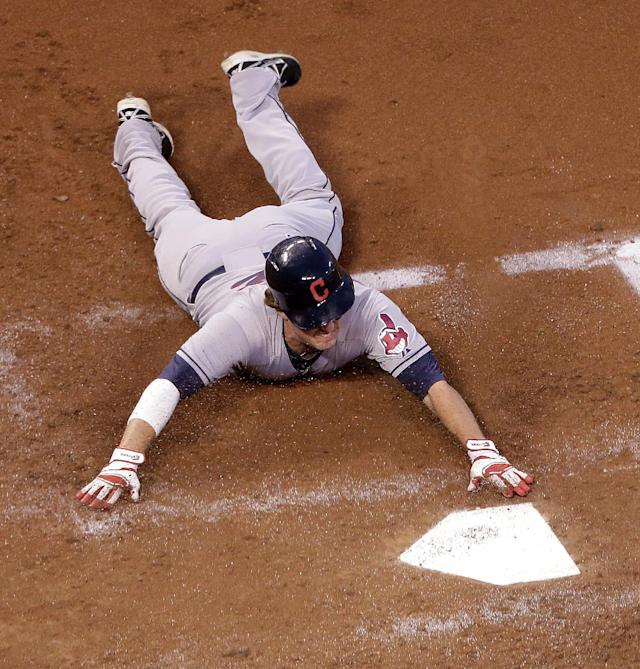 Cleveland Indians' Tyler Holt slides home to score on a single by Jose Ramirez during the third inning of a baseball game against the Kansas City Royals Friday, Aug. 29, 2014, in Kansas City, Mo. (AP Photo/Charlie Riedel)