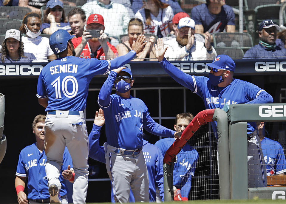 Toronto Blue Jays' Marcus Semien (10) is congratulated after scoring in the ninth inning of a baseball game against the Atlanta Braves Thursday, May 13, 2021, in Atlanta. Semien scored on a double by Blue Jays' Bo Bichette. (AP Photo/Ben Margot)
