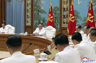 """In this photo provided by the North Korean government, North Korean leader Kim Jong Un, second left in the background, attends an emergency Politburo meeting in Pyongyang, North Korea Saturday, July 25, 2020. Independent journalists were not given access to cover the event depicted in this image distributed by the North Korean government. The content of this image is as provided and cannot be independently verified. Korean language watermark on image as provided by source reads: """"KCNA"""" which is the abbreviation for Korean Central News Agency. (Korean Central News Agency/Korea News Service via AP)"""