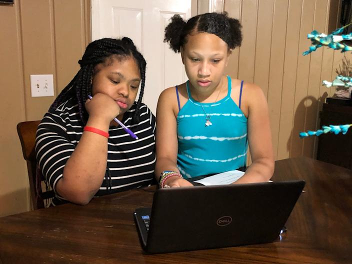 Abigail Alexander (right), a fifth grader at Head Middle Magnet School, helps her sister Anaya Alexander (left), an exceptional education student at Maplewood High School, try to log online for the first day of virtual learning for Metro Nashville Public Schools on Tuesday, Aug. 4.
