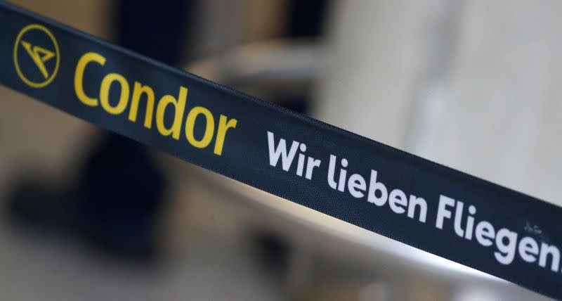 "A banner reding ""Condor we love flying"" is seen next to a check-in counter of airline Condor at the airport in Frankfurt"