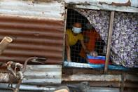A woman peers out from her shack as firefighters and volunteers disinfect a street in Yangon