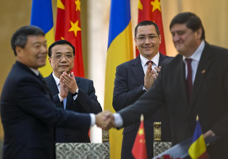 China's Premier Li Keqiang, left background, applauds with Romanian counterpart Victor Ponta, centre right, during the signing of bilateral agreements at the government headquarters in Bucharest, Romania, Monday, Nov. 25, 2013. China's Premier will attend the China - Central and Eastern Europe meeting of heads of government, starting Tuesday in the Romanian capital. (AP Photo/Vadim Ghirda)