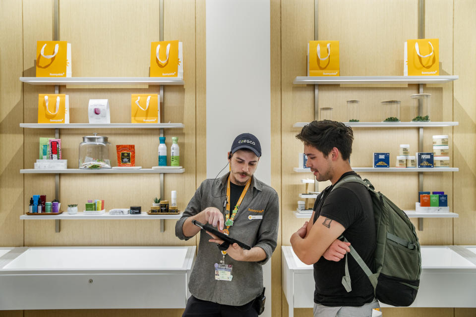 Paul Melone, left, helps customer Brandon Nguyen, 27, at the Sunnyside dispensary in Chicago's River North neighborhood on July 28, 2021. The dispensary is the closest marijuana shop to the Lollapalooza music festival. (Armando L. Sanchez/Chicago Tribune via AP)