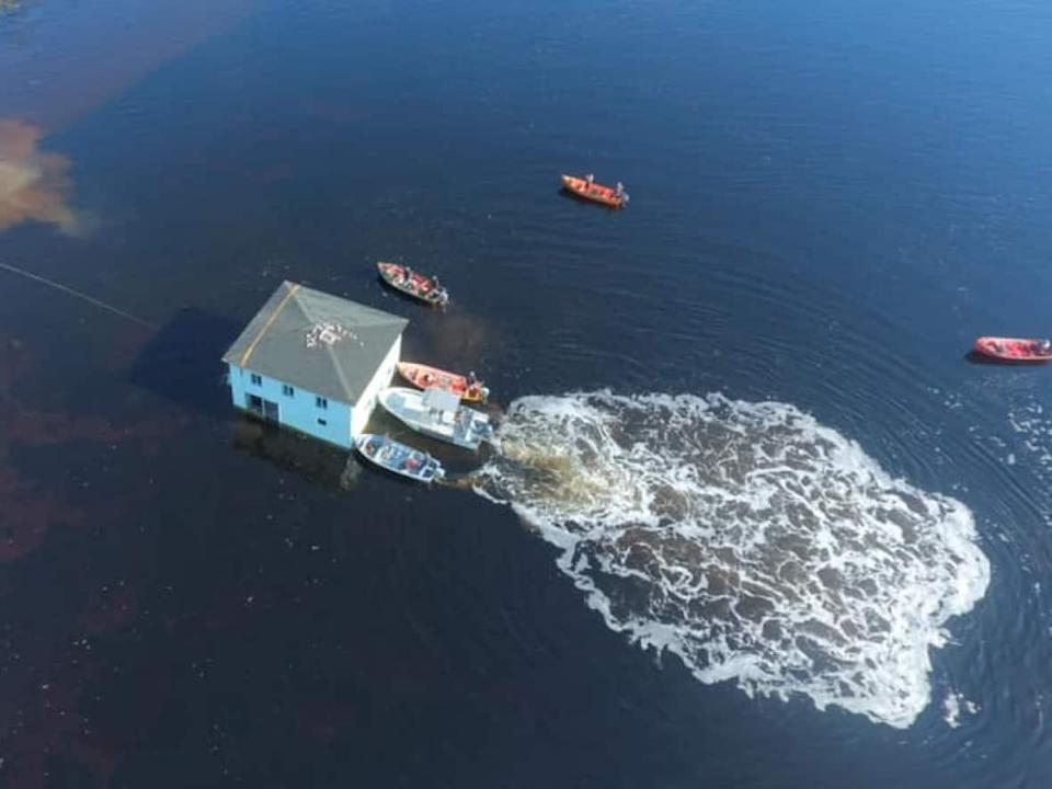 Daniele Penney and her boyfriend Kirk Lovell got their dream home by moving it about one kilometre down the north shore of the Bay of Islands — a 'nail-biting' effort, she says, that took eight hours and a half-dozen boats. (Submitted by Keith Goodyear - image credit)