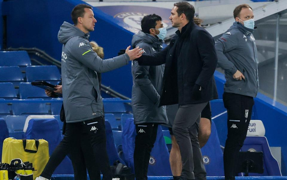 Terry greets then-Chelsea boss Frank Lampard on the sidelines at Stamford Bridge last year - NMC POOL