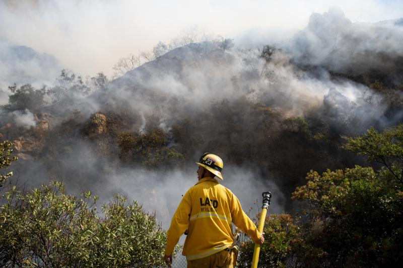 A firefighter looks out over the flames of the Palisades Fire minutes after it ignites on Monday, Oct. 21, 2019 in the Pacific Palisades, section of Los Angeles. The blaze broke out Monday morning in a coastal canyon of the affluent Pacific Palisades neighborhood. The flames quickly churned uphill through dry brush as helicopters made water drops to keep it from reaching large houses at the top of a bluff. (AP Photo/Christian Monterrosa)