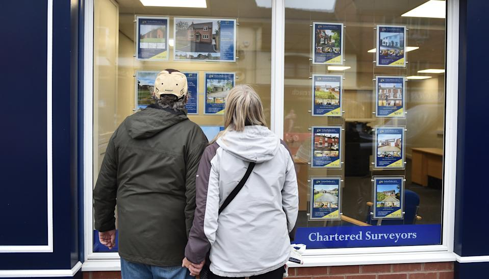 LEEK, ENGLAND - NOVEMBER 11: A couple are seen looking at houses for sale at an estate agents in Market Town of Leek on November 11, 2020 in Leek, England. The United Kingdom will continue to impose lockdown measures until December 2 in an attempt to curb transmissions of the coronavirus (COVID-19)   (Photo by Nathan Stirk/Getty Images)