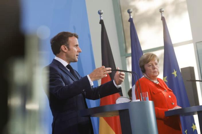 German Chancellor Angela Merkel and French President Emmanuel Macron give a news statement in Berlin