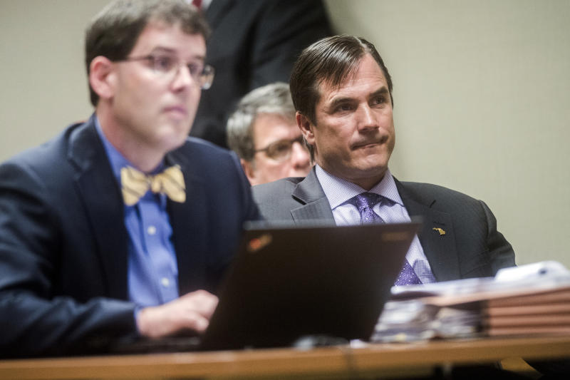 Nick Lyon, right, director of the Michigan Department of Health and Human Services, listens closely as Genesee District Judge David J. Goggins gives his decision during Lyon's preliminary examination on Monday, Aug. 20, 2018 at Genesee District Court in Flint, Mich. Goggins ordered Lyons to stand trial for involuntary manslaughter in two deaths linked to Legionnaires' disease in the Flint area, the highest ranking official to stand trial as a result of the tainted water scandal. (Jake May/The Flint Journal via AP)