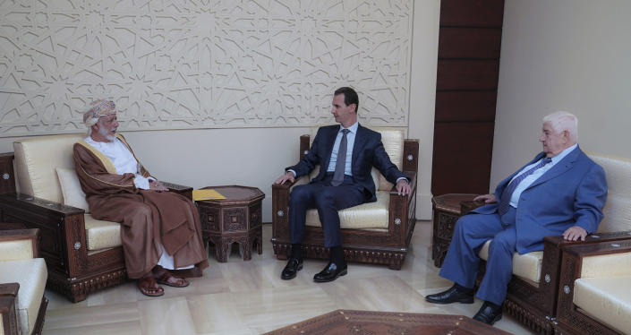 In this photo released by the Syrian official news agency SANA, Syrian President Bashar Assad, center, meets with Oman's Foreign Minister Yusuf bin Alawi, left, and Syrian Foreign Minister Walid Muallem, right, in Damascus, Syria, Sunday, July 7, 2019. Alawi made a rare visit to Damascus where he discussed with President Bashar Assad ways of restoring stability and security in the region.(SANA via AP)